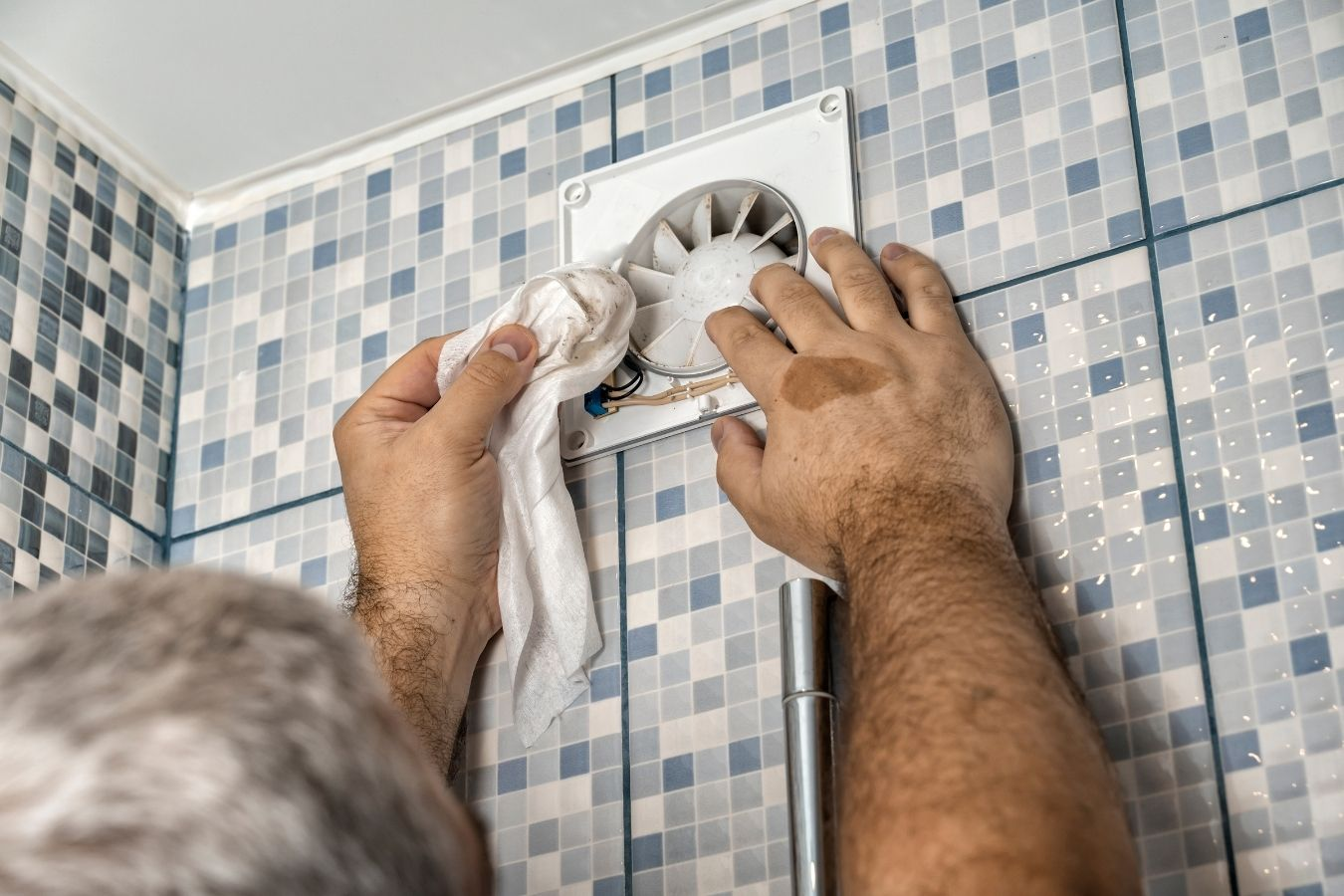 A man installing a through the wall exhaust fan in a bathroom
