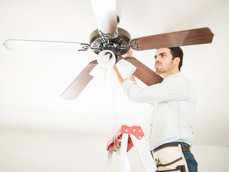 A person replacing ceiling fan blades